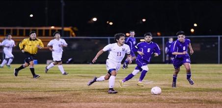 Senior Pablo Henriquez dribbles the ball up field past two defenders in Bastrop's scrimmage against LBJ on Jan. 12. The Bears fought hard but came up short with a loss of 1-0.