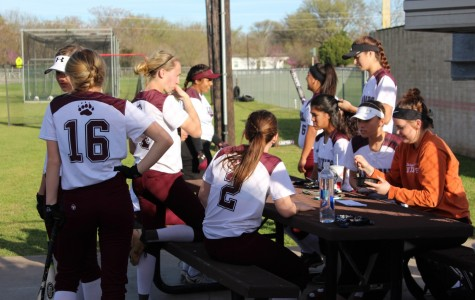 Just before the game, junior Carely Soules (far right) supports her Lady Bear softball team. Her teammates are getting ready to warm up on the field.
