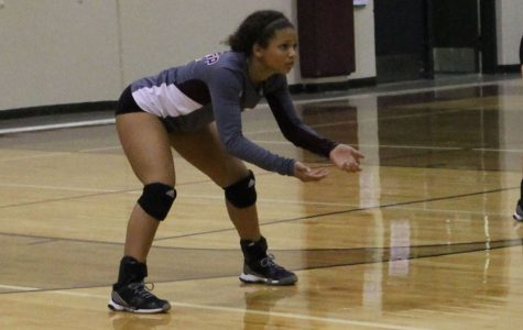 Freshman Caela McGee gets ready to hit the ball to her teammate. She is focused and prepared to make contact.