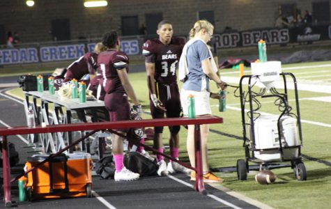 Trainer Laura Mueller fills up the water bottles for the football players at the sideline of the football field. The trainers learn in the sports medicine class that it is important to make the players stay hydrated, so they can put maximal effort in the game.