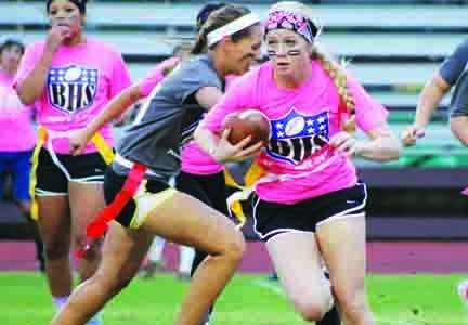 Junior running back Taylor Langle sneaks through the secondary and looks to get the first down in the 2014 PowderPuff football game at Erhard Field.