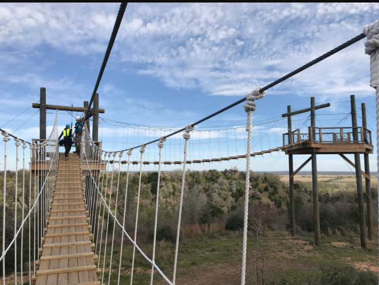 Zip-liners+walk+from+platform+to+platform%2C+preparing+to+zip+line+while+crossing+over+the+gorgeous+hill+country+of+Bastrop+and+Cedar+Creek.+