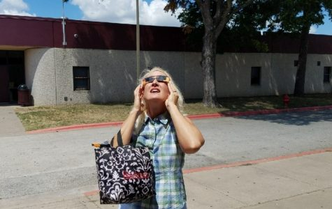Spanish teacher, Lisa Hutchinson enjoys the view of the partial solar eclipse using eclipse glasses purchased by Paula Rodriguez, a Bastrop High School counselor. Hutchinson is accompanied by many teachers and students, excited about the partial totality of the solar eclipse.