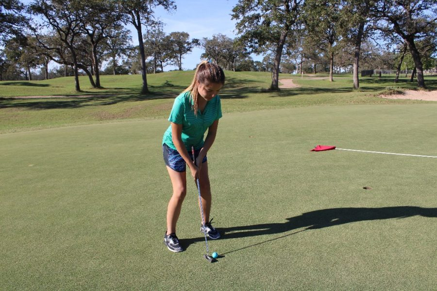 Junior+Zoe+Robinson+lines+up+the+golf+ball+strategically+with+the+hole+so+that+she+is+able+to+make+the+putt+in+one+shot.+