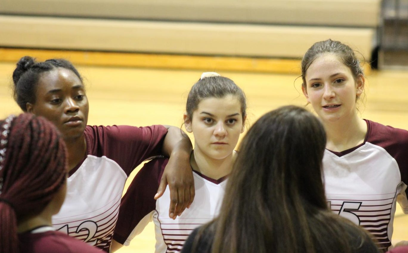 During their intense game against Hutto, seniors Demonaye Rector(left), Gracie Long(middle) and Amanda Branecky(right) listen to volleyball coach Nicole Creek as she talks strategy with the team. Bastrop held a close game with the top team in Central Texas 5A, taking one set from them, but ended up losing 3-1. Hutto volleyball comes to BHS on October 2 to face off with the Lady Bears again this season.
