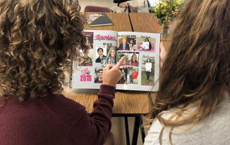 "Reminiscing on last year's memories, students look at the 2017-2018 senior superlatives page in the Bear Tracks. The senior superlatives page highlights certain students for things like ""best dressed"", ""most changed"", ""life of the party."" ""I think senior superlatives are really cool and fun,"" junior Logan Anderson said. ""But some of them can be taken inappropriately and it's kind of like a popularity contest, so it makes sense why the yearbook is limiting them."""