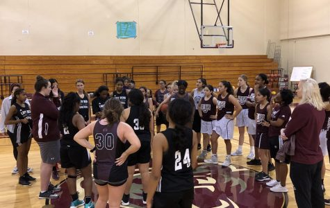 The girls' basketball team circles up after practice with 3 of their 4 new coaches.