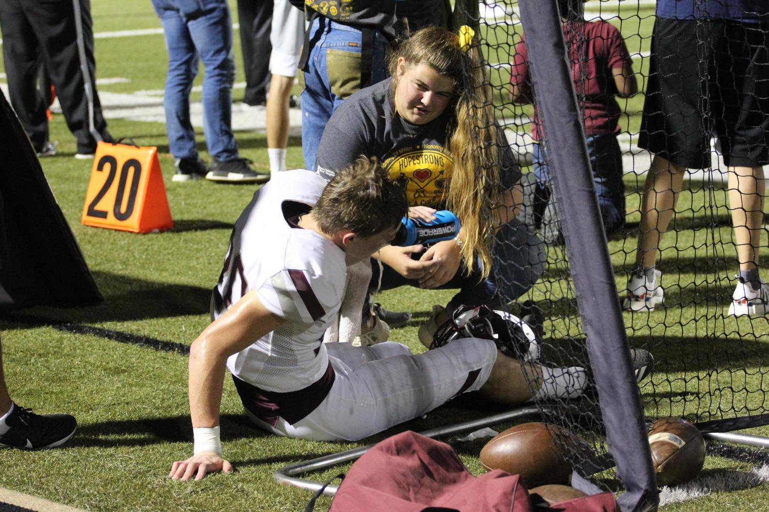 Senior advanced athletic trainer Reagan Ferem tends to an injured varsity football player at the coveted Bastrop vs Cedar Creek Gold Out game on October 4 at Memorial stadium.