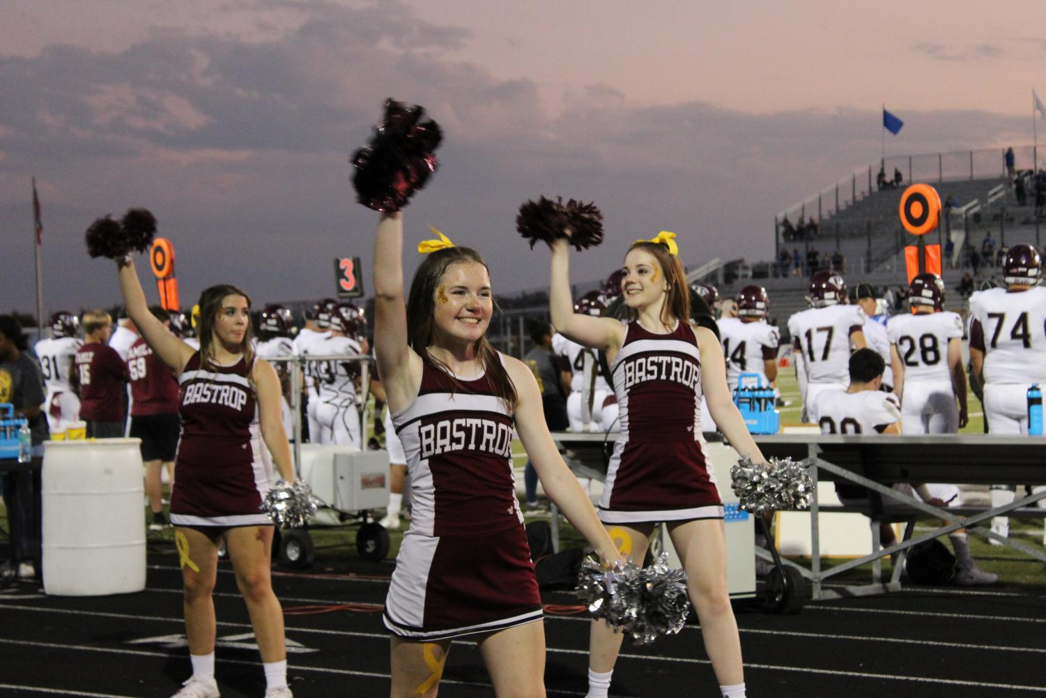 Senior Mary Smalley, and sophomores Madeline Coats and Madeleine Aston hype up the crowd at the Bastrop Gold Out game on October 4 at Memorial stadium.