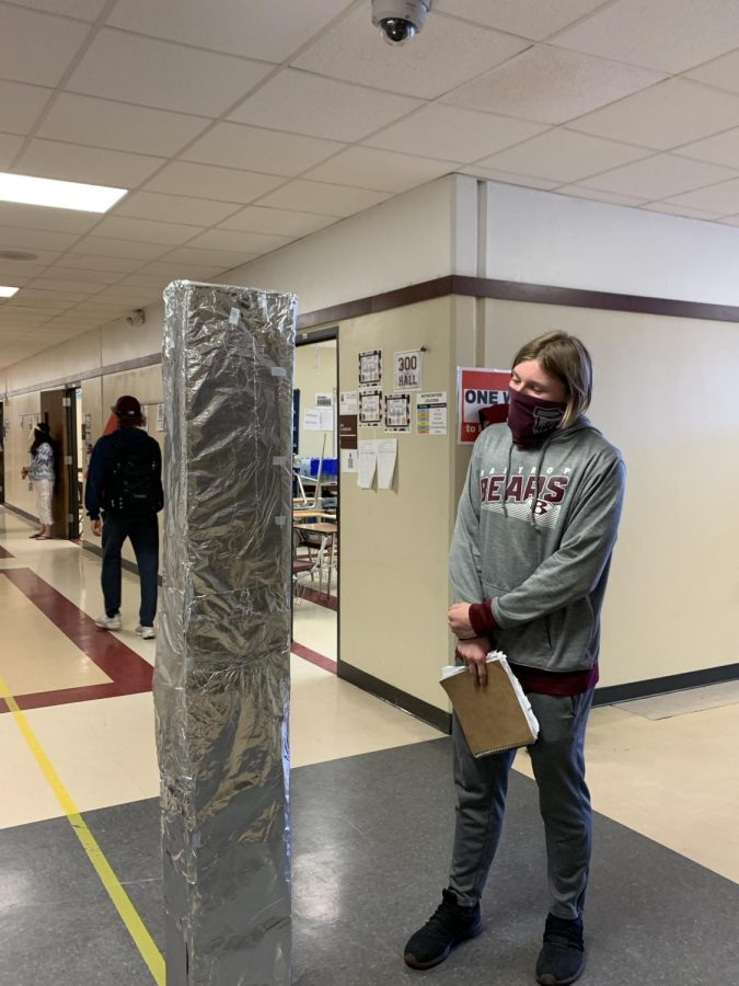 Senior Kef Kellum pauses during the passing period to gawk at the mysterious monolith in the 300 hall.