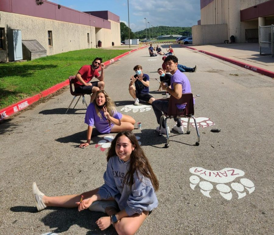 Members of the Class of 2021 paint bear paws on Bear Drive at a Key Club organized event. To participate, seniors donated $20 to the charity of their choice.